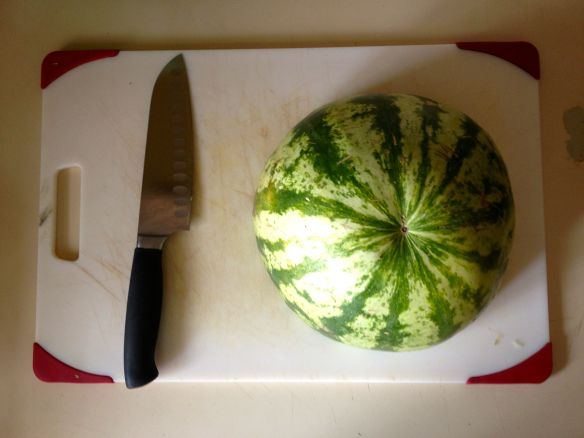 Half of a watermelon on a cutting board with a santoku knife
